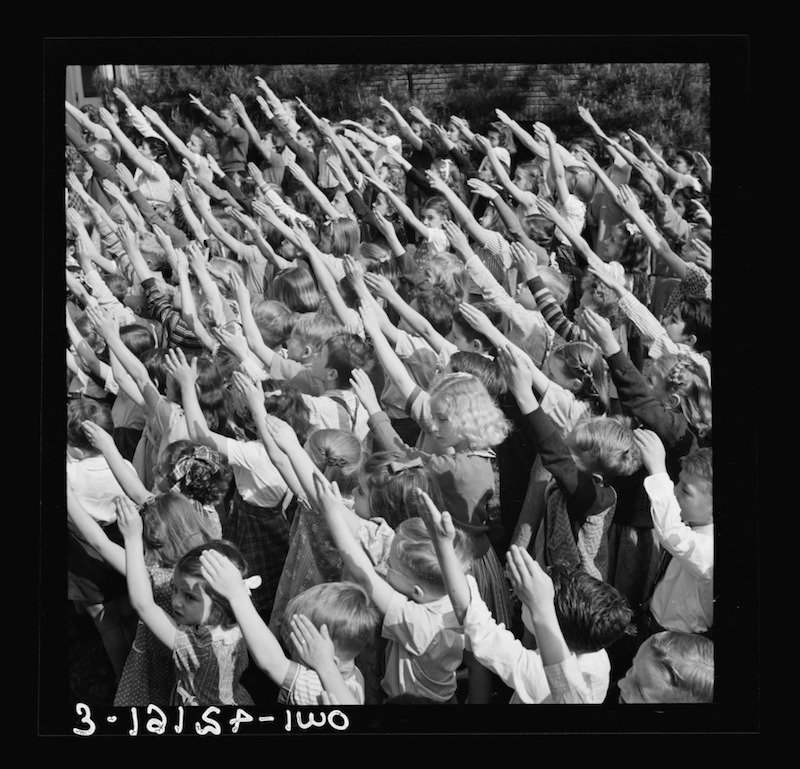 B& W photo of 1940s School students in saying the Pledge of Allegiance with the Bellamy salute, which looks similar to the Hitler salute.