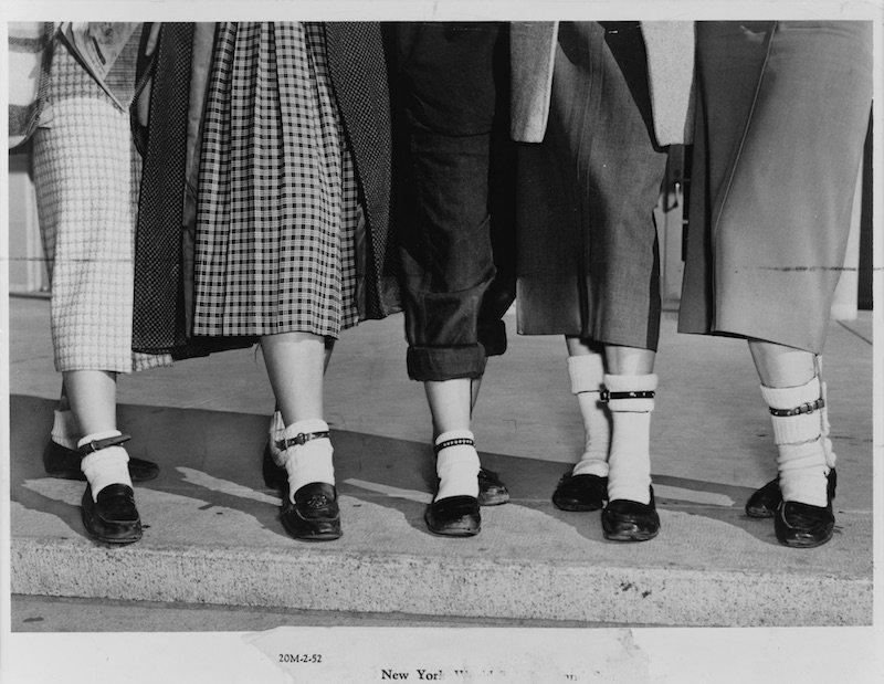 black and white photo of girls ankles in white socks and dog collars as anklets around the white socks